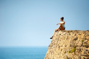 Woman sitting on a rock looking at the blue sky in self awareness after meditating.